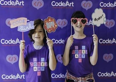 students in photobooth with props